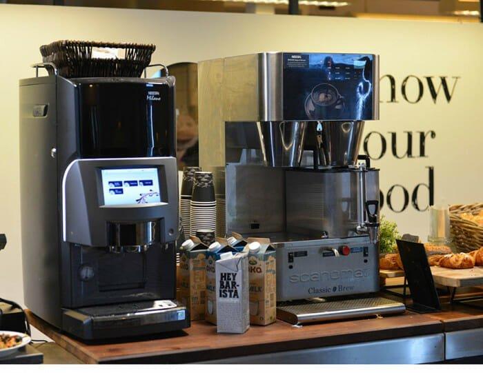 Billede af kaffemaskiner på et bord. Mælk og croissanter ved siden af. Billig kaffe på Gimle.